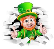 Cartoon Leprechaun St Patricks Day. A cute St Patricks Day Leprechaun cartoon character breaking through the background brick wall and giving a thumbs up Stock Photos
