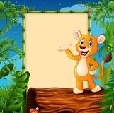 Cartoon lion standing on hollow log near the empty framed signboard Royalty Free Stock Photography