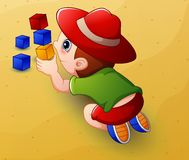 Cartoon little boy playing with cubes toys in sand Royalty Free Stock Photo
