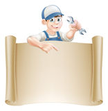 Cartoon mechanic and scroll. A mechanic or plumber holding an adjustable spanner or wrench and peeking over a scroll sign and pointing Stock Photography