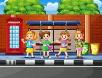 Free Cartoon Of School Children In The Bus Stop With A Teacher Stock Photography - 133336972