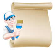 Cartoon Painter Decorator Sign. A cartoon painter decorator in a cap hat and blue dungarees holding a paintbrush tool and peeking around a scroll Stock Images
