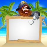Cartoon pirate beach sign. Illustration of a fun cartoon pirate pointing over a sign on a beach Stock Photo