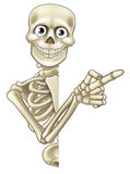 Cartoon Pointing Skeleton. A skeleton Halloween cartoon character peeping around a sign and pointing at it Stock Photo