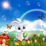 Cartoon rabbit decorating an Easter egg with nature background. Illustration of Cartoon rabbit decorating an Easter egg with nature background Royalty Free Stock Photo