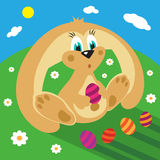 Cartoon rabbit with easter eggs on the grass Stock Image