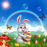 Cartoon rabbit holding an Easter egg with nature background Royalty Free Stock Image