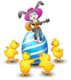 Cartoon rabbit playing guitar on a large egg is decorated and surrounded by chicks Royalty Free Stock Image
