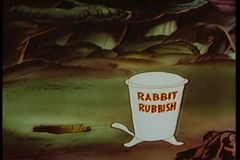 Cartoon of rabbit throwing rubbish out of a hole and into a trash can stock video