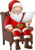 Cartoon Santa Claus sitting at his armchair and reading a letter Stock Photo