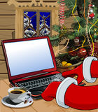 Cartoon Santa Claus writes a letter on the laptop. In a wooden house Stock Image