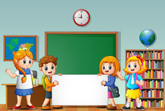 Cartoon school kids with blank sign in a classroom Stock Photo
