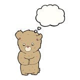 Cartoon shy teddy bear with thought bubble Stock Photos