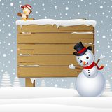 Cartoon snowman with a owl and a snowy wooden signboard Stock Image