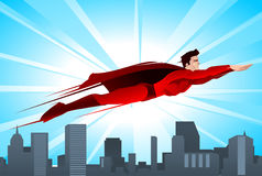 Cartoon Super hero flying over a city. Shining superhero flying over the city, with red suit and red cape vector illustration Stock Photo