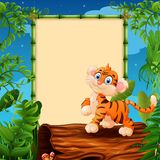 Cartoon tiger on hollow log near the empty framed signboard Royalty Free Stock Images