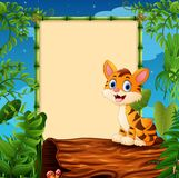 Cartoon tiger sitting on hollow log near the empty framed signboard. Illustration of Cartoon tiger sitting on hollow log near the empty framed signboard Royalty Free Stock Photos