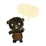 Cartoon waving black bear cub with speech bubble Stock Photography