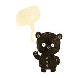 Cartoon waving black bear cub with speech bubble Royalty Free Stock Images