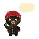 Cartoon waving black teddy bear in winter hat with speech bubble Stock Photography