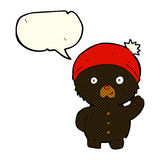Cartoon waving black teddy bear in winter hat with speech bubble Stock Image