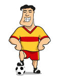 Cartoonhappy football or soccer player. Professional soccer or football player cartoon character in yellow and red sporting uniform standing with one leg on the Stock Image
