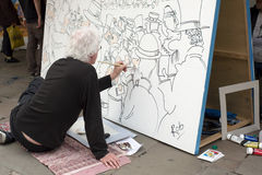 Cartoonist at Work. Cartoonist drawing a large scale cartoon at an international cartoon festival. Shrewsbury, England