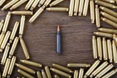 Cartouches d'Ak-47 sur le plan rapproché en bois de table Photographie stock libre de droits
