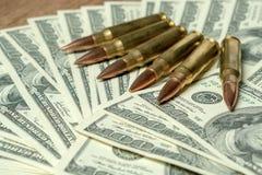 6 cartouches de fusil sur cent billets d'un dollar Concept pour le crime, massacre de contrat, assassin payé, terrorisme, guerre, photographie stock