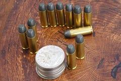 Cartouches de revolver et période occidentale sauvage de dollar en argent sur le fond en bois Photos stock