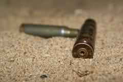 Cartouches vides sur le sable Photographie stock libre de droits