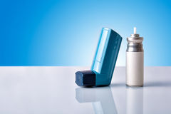 Cartridge and blue medicine inhaler with blue background front v Royalty Free Stock Images
