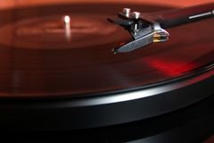 Cartridge of a modern high quality turntable record player about to be lowered onto a vinyl analogue music LP with red backlight.  Stock Photo