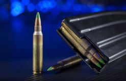 Ammo for AR-15s. Cartridges and a magazine for an AR-15 with a blue background Royalty Free Stock Photography