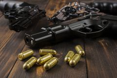 Cartridges, revolvers, pistols. Two revolvers, one pistol with cartridges on a wooden table Stock Photo
