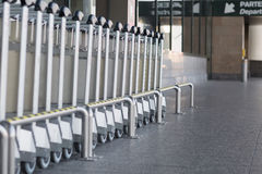 Carts to transport luggage to airport. Push; traveler; pens; terminal; tram; tourism; angle; up; drive; exit; shut down; line; metal; unusual Stock Photos