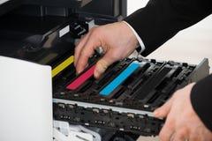Cartucho de la fijación del hombre de negocios en máquina de fotocopia Imagen de archivo libre de regalías