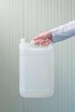 Cartucho plástico branco do tanque na mão fêmea Fotos de Stock