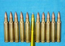 Cartucho 5 um calibre de 56 milímetros com pena como um conceito da propaganda nos mass media Conceito falsificado da invasão da  Fotografia de Stock