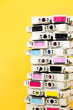 Cartuchos de tinta esgotados empilhados no fundo amarelo Imagens de Stock