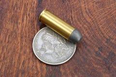 Cartuchos do revólver e período ocidental selvagem do dólar de prata no fundo de madeira Foto de Stock Royalty Free