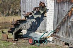 Cartuchos para o carrinho de mão diesel e manual do jardim perto do celeiro quebrado abandonado da vila fotos de stock royalty free