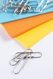 Cartulina coloreada con los paperclips en una tabla blanca Fotografía de archivo