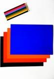 Cartulina coloreada y lápices coloreados en el fondo blanco Imagen de archivo libre de regalías