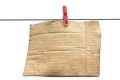 Cartulina con la ropa-clavija en el alambre Imagenes de archivo