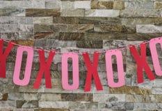 Cartulina cortada Xs y OS para los abrazos y los besos picados en el hilado y colgados en la pared de la roca - decoración de las imagenes de archivo