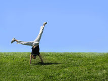 Cartwheel. Girl is doing a cartwheel on the grass royalty free stock photo