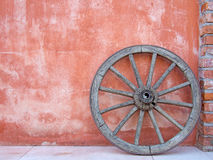 Cartwheel against terracotta wall, Italy. Royalty Free Stock Image