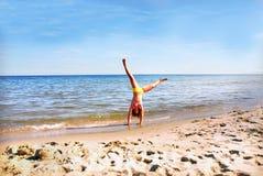 Cartwheel on the beach. Teenage girl making cartwheel on the beach Royalty Free Stock Image