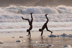 Cartwheel Children. Two young boys express their freedom with handstands on the beach Royalty Free Stock Photo